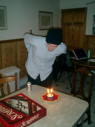 blowing out the candles on my 23rd birthday cake in a black hat and blue shirt