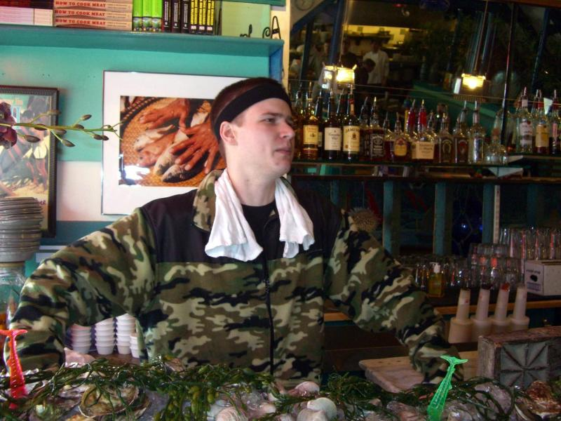 Shucking oysters at the East Coast Grill in camo with a sweatrag and a headband